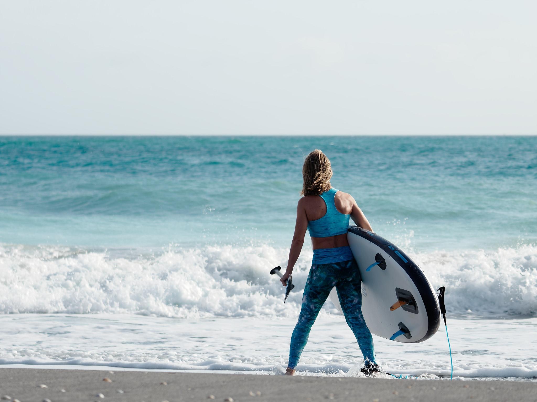 Paddle board rider near waves